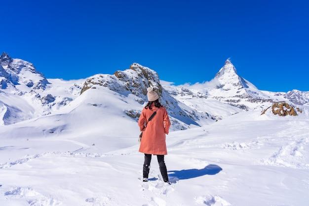 Turista de la mujer joven que goza con el pico de matterhorn de la montaña de la nieve en el día de invierno, zermatt, suiza. Foto Premium