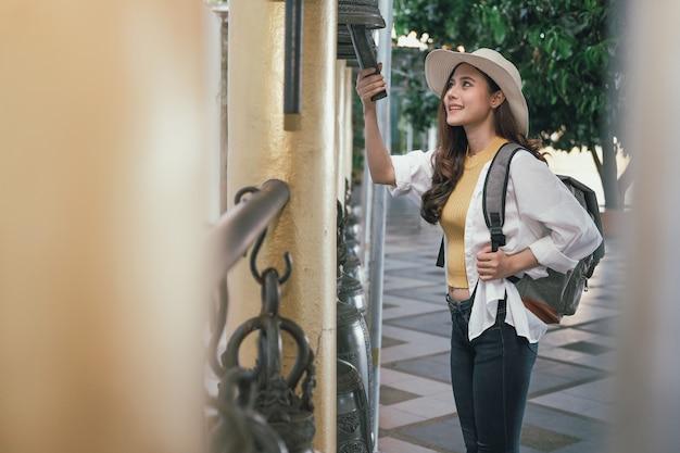 Turista de mujer viajero tocando la campana en el templo. viaje viaje viaje Foto Premium
