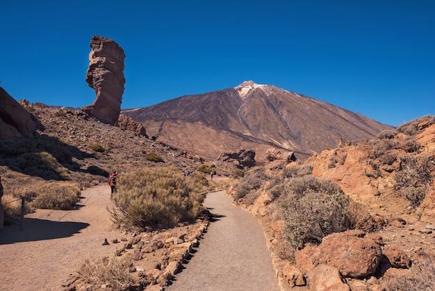 Turista no identificable caminando en el parque nacional del teide en un día soleado tenerife, isla canaria Foto Premium