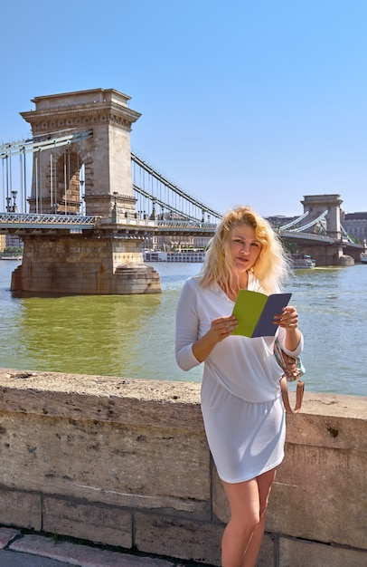 Turista en vestido blanco frente al famoso puente de las cadenas en budapest Foto Premium