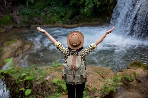 Las turistas están felices y descansadas en la cascada. Foto gratis