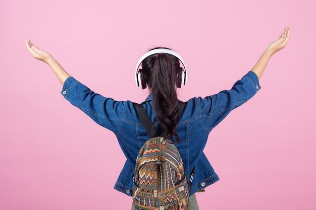 Turistas femeninos en el estudio en un fondo rosado. Foto gratis