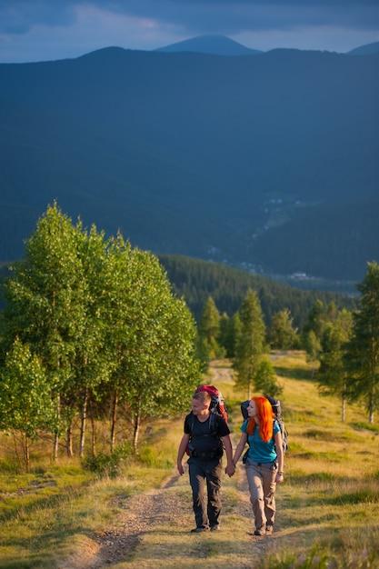 Turistas, hombres y mujeres con mochilas caminando por una hermosa zona de montaña, tomados de las manos Foto Premium
