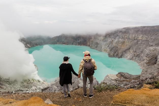 Los turistas de la pareja miran el lago del azufre en el volcán ijen en la isla java en indonesia. los excursionistas viajan en la cima de la montaña, concepto de viaje Foto Premium