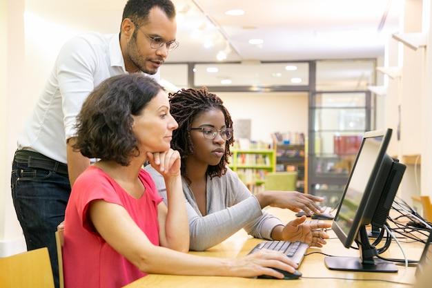 Tutor ayudando a estudiantes en clase de computación Foto gratis