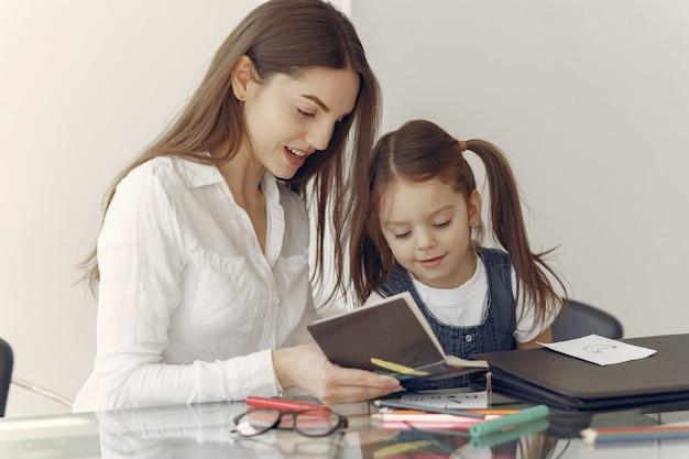 Tutor con litthe girl estudiando en casa Foto gratis