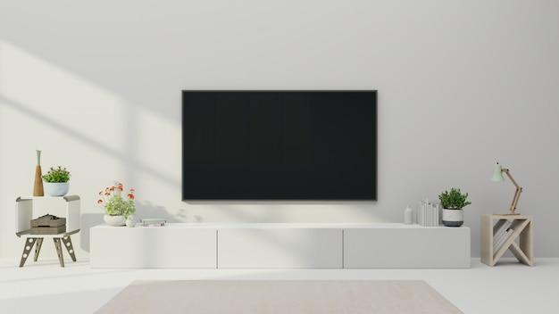 Tv en el gabinete en la moderna sala de estar con planta sobre fondo de pared blanca. Foto Premium