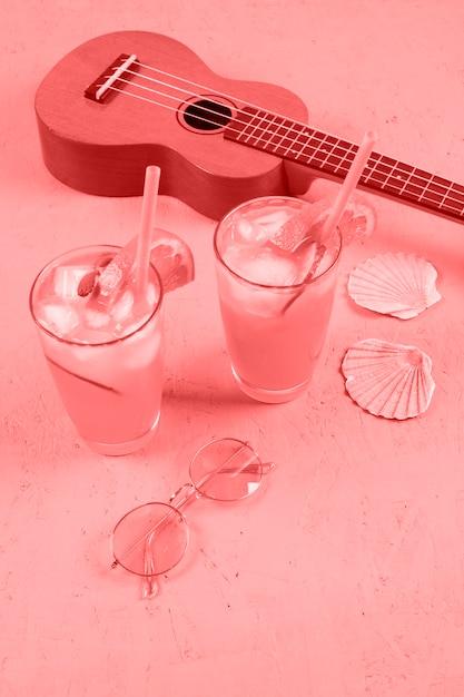 Ukelele copas de cóctel; conchas de vieira y gafas de sol sobre fondo coral Foto gratis