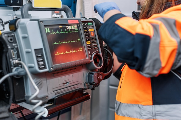 Urgencia médica en la ambulancia. médico de urgencias con desfibrilador. Foto Premium