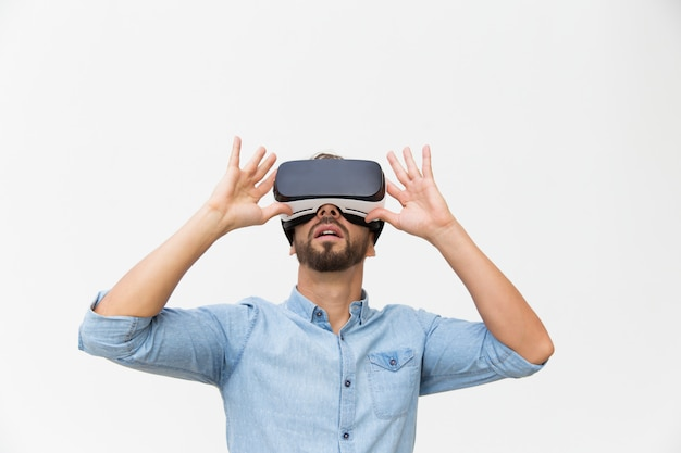 Usuario masculino emocionado con gafas vr, dispositivo táctil Foto gratis