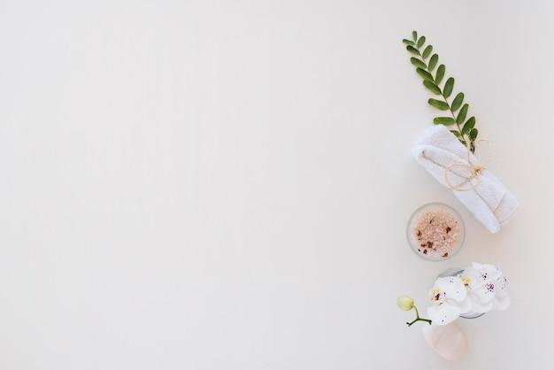 Utensilios de baño y sal rosa colocados en mesa blanca Foto gratis