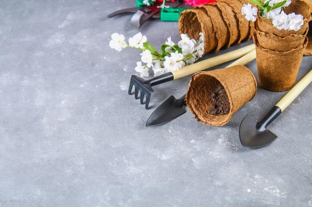 Utensilios de jardinería, potes en un fondo concreto gris. copia el espacio. Foto Premium