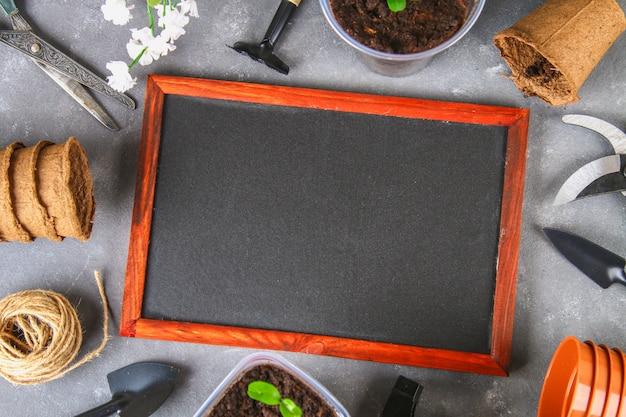 Utensilios de jardinería y potes en un fondo concreto gris. tablero de tiza vista superior, copia espacio. Foto Premium