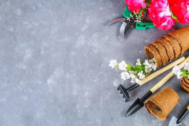 Utensilios de jardinería y potes en un fondo concreto gris. vista superior, copia espacio. Foto Premium