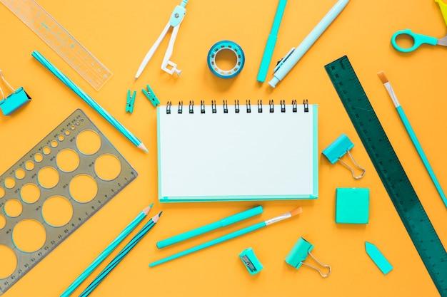 Útiles escolares con cuaderno en blanco en el centro Foto gratis