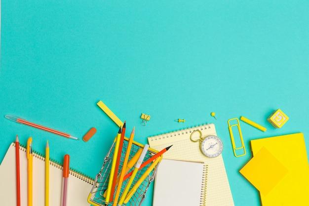 Útiles escolares en el fondo de papel colorido Foto Premium