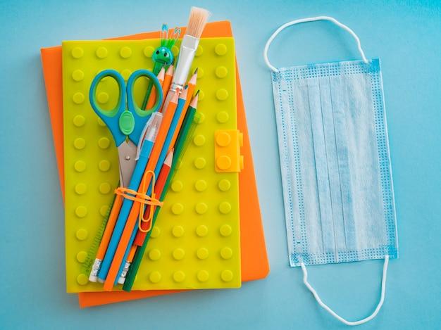 Útiles escolares con mascarilla médica en azul azul. plano, vista superior, diseño, plantilla, espacio libre Foto gratis