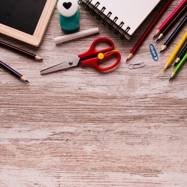 Útiles escolares en superficie de madera Foto gratis