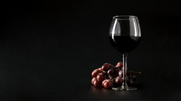 Uva cerca de un vaso de vino Foto gratis