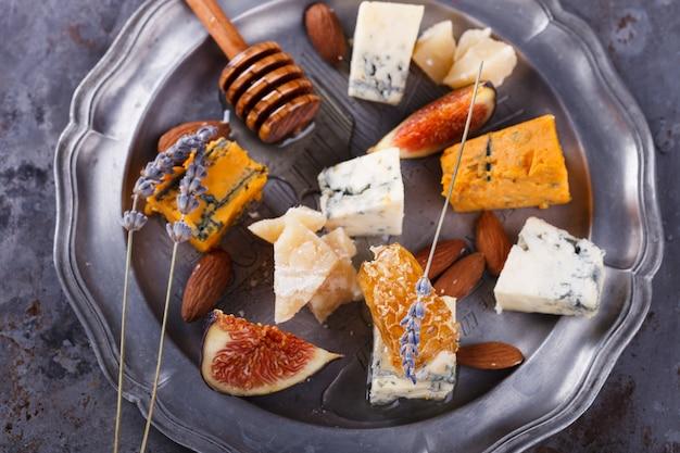 Uva, queso, higos y miel. plato de queso. Foto Premium