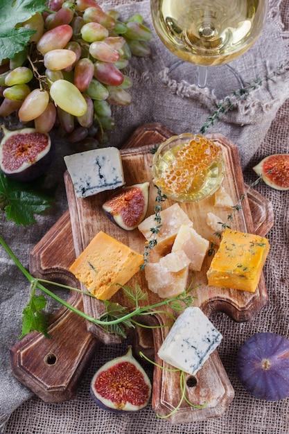 Uva, queso, higos y miel. tablero de queso. Foto Premium