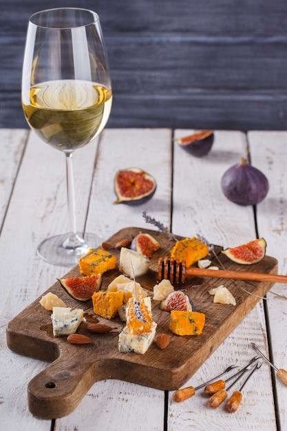 Uva, queso, higos y miel con un vaso de vino tinto y blanco sobre una tabla de madera Foto Premium