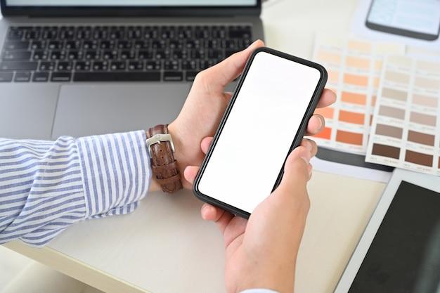 Ux ui diseñador sosteniendo un teléfono móvil con pantalla en blanco Foto Premium