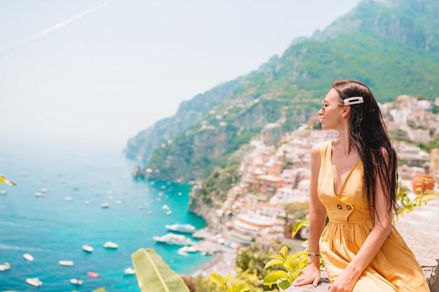 Vacaciones de verano en italia. mujer joven en el pueblo de positano en el fondo, costa de amalfi, italia Foto Premium