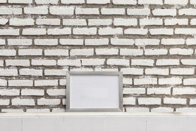 Vacíe el marco blanco en la pared de ladrillos grunge, simúlpelo para mostrar o el montaje de su contenido. Foto Premium