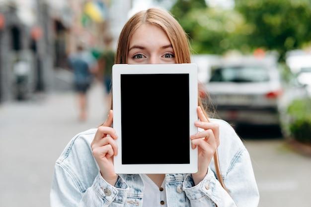 Vacie la pantalla negra del ipad de la maqueta en manos femeninas. chica asomando por detrás de una pantalla Foto Premium