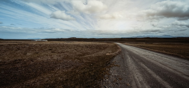 Vacío camino de tierra a través del paisaje rural. Foto Premium