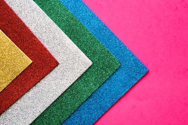 Varias alfombras coloridas en fondo rosado Foto gratis