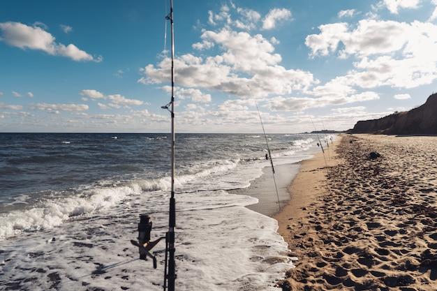 Varias cañas de pescar en una fila en la playa Foto gratis