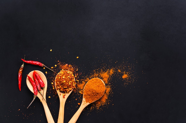 Varias especias de chile seco en cucharas de madera sobre fondo negro, vista superior Foto Premium