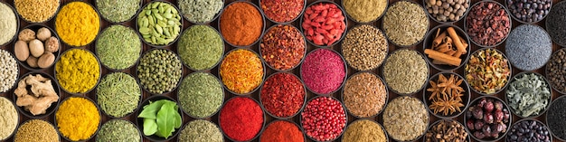 Varias especias y hierbas como fondo. condimentos coloridos en tazas, vista superior. Foto Premium