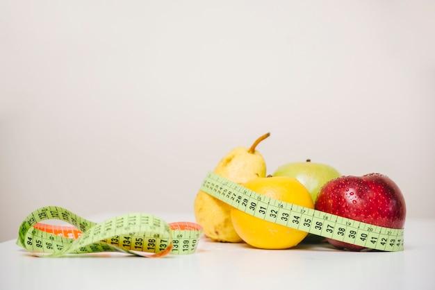 Varias frutas sanas y cinta métrica en la mesa Foto gratis