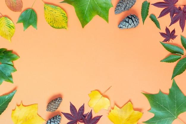 Varias hojas de otoño y piñas sobre un fondo naranja, vista desde arriba Foto Premium