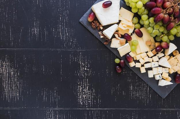 Variedad de bloques de queso con uvas sobre fondo negro con textura Foto gratis