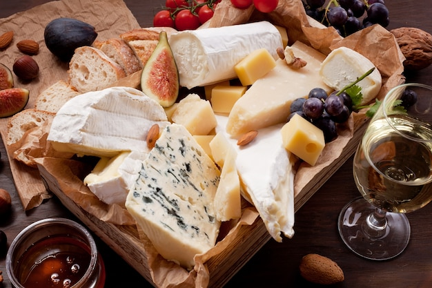 Variedad de diferentes quesos con vino, frutas y nueces. Foto Premium