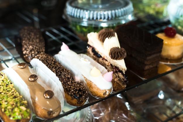 Variedad de eclairs y deliciosos pasteles de repostería en la vitrina. Foto gratis