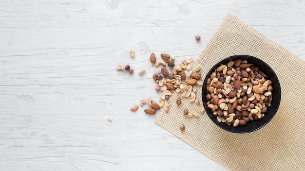 Variedad de frutos secos en mantel sobre fondo de madera Foto gratis