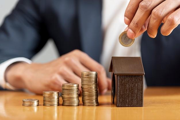 Variedad de montones de monedas y caja de dinero de la casa. Foto gratis