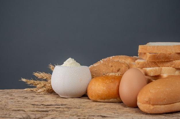 Variedad de pan en la tabla de madera en un viejo fondo de madera. Foto gratis