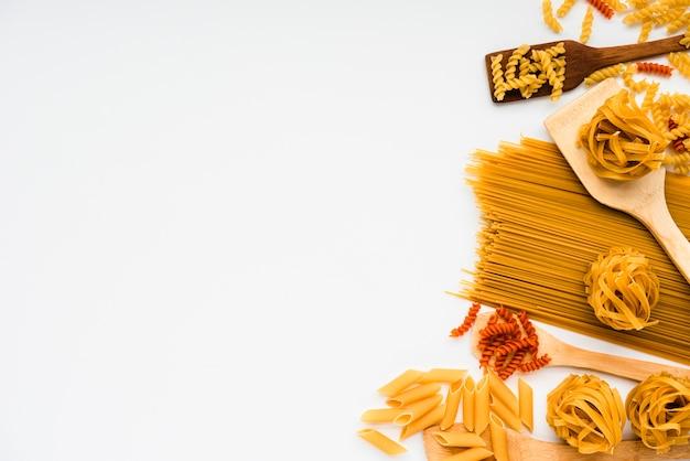 Variedad de pasta italiana cruda y espátula de madera sobre fondo blanco. Foto gratis