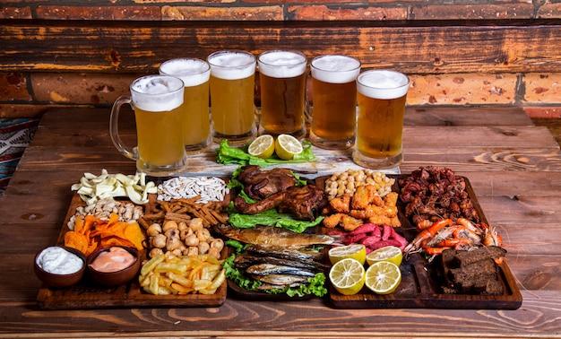 Variedad de snacks y frutos secos con vasos de cerveza. Foto gratis