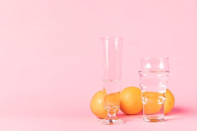 Variedad de vasos llenos de agua y naranjas. Foto gratis