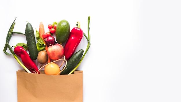 Variedad de verduras en bolsa de papel sobre fondo blanco Foto gratis