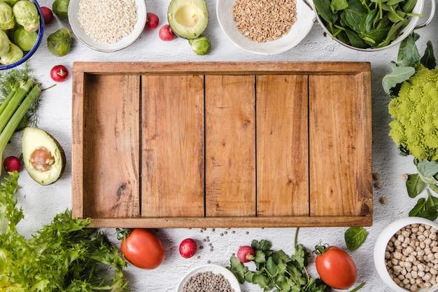 Una variedad de verduras de temporada y granos enteros colocados sobre una superficie blanca y una bandeja de madera vacía Foto Premium
