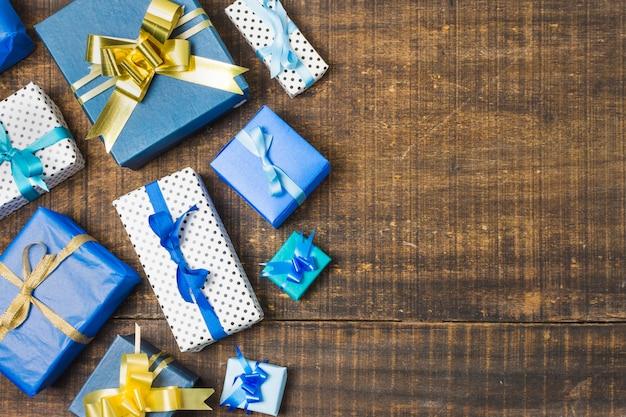 Vario regalo en caja envuelto y decorado con cintas sobre una vieja mesa desgastada Foto gratis