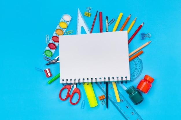 Varios artículos de papelería en forma de lápices, rotuladores, bolígrafos, tijeras, clips de papel, botellas de pintura Foto Premium